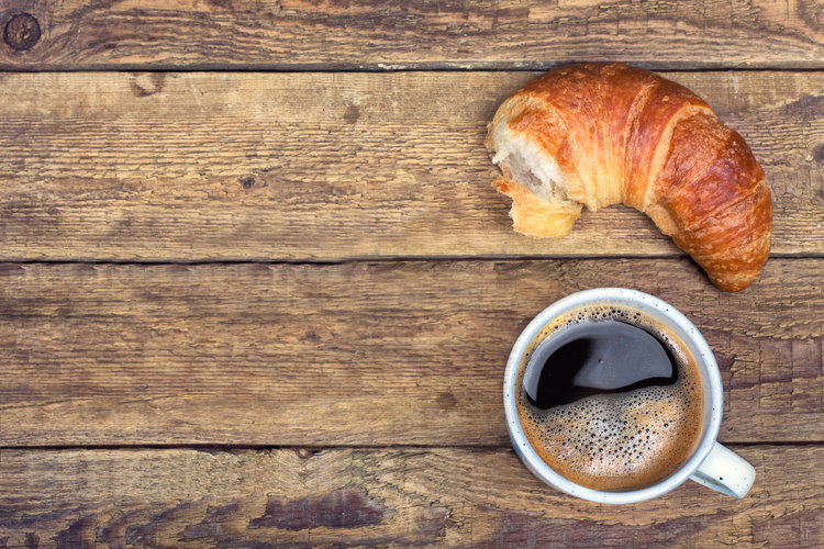 Coffee and croissant for breakfast on rustic wooden table, top view